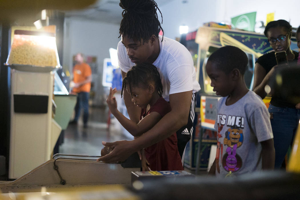 Azo McMiller bowls with daughter Azalea, 5, and son Azo Jr., 7, at the Pinball Hall of Fame in ...