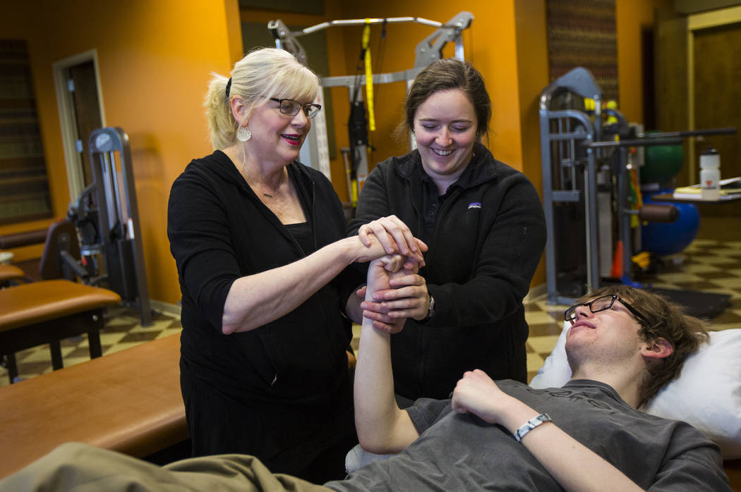 Student physical therapist Meghan Bell, upper right, demonstrates exercises to Kay McClure, lef ...