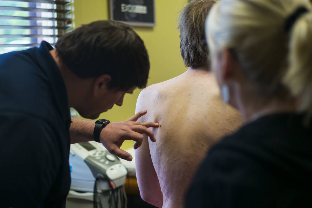 Physical therapist Walker Gardner, left, examines Grayson McClure at EXOS Physical Therapy & Sp ...