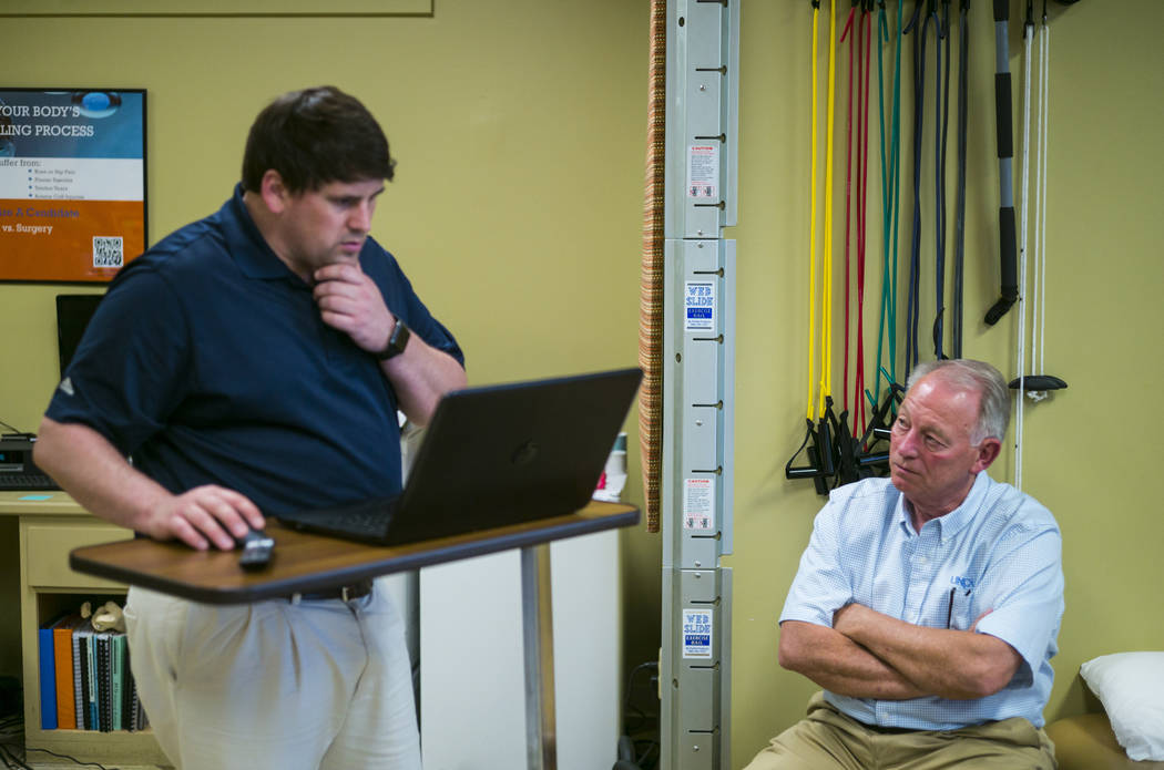 Physical therapist Walker Gardner, left, talks with Terry McClure at EXOS Physical Therapy &amp ...