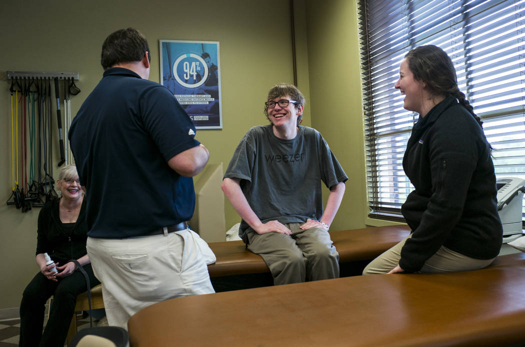 Grayson McClure, center, and his mother, Kay McClure, left, talk with physical therapists Walke ...