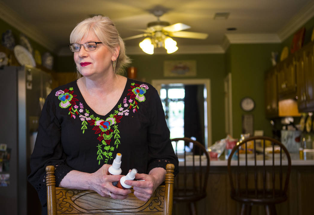 Kay McClure holds a pair of oral sprays used by her son, Grayson, at their home in Collierville ...