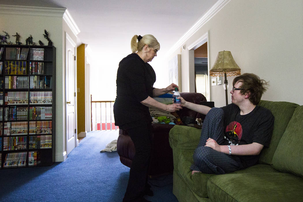 Kay McClure gives her son, Grayson McClure, morning medication at their home in Collierville, T ...