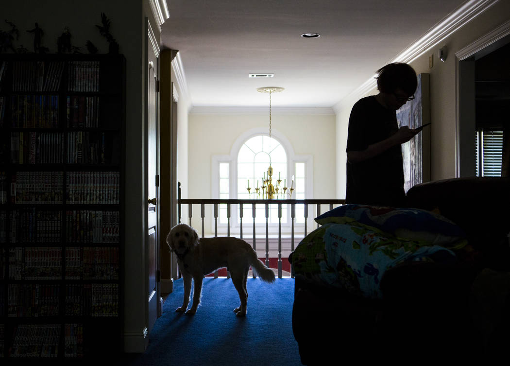 Grayson McClure checks his phone while standing next to his dog, Yojimbo, at the McClure's home ...