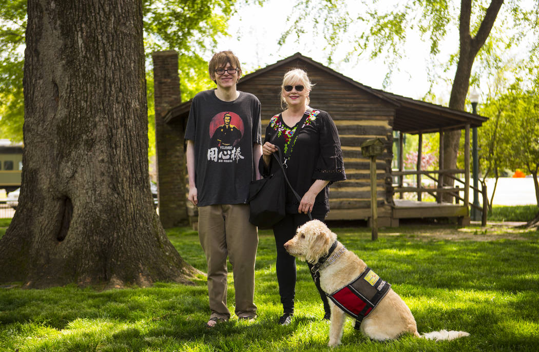 Grayson McClure, left, stands with his mom, Kay McClure, and service dog Yojimbo, at the park a ...