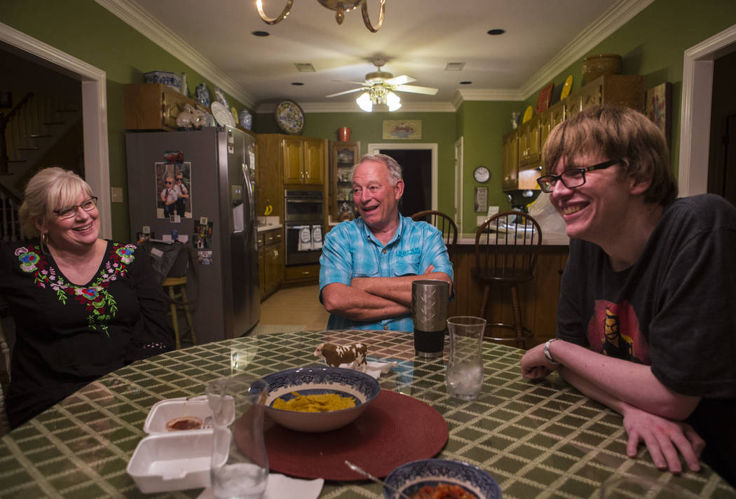 Grayson McClure, right, shares a laugh with his parents, Kay McClure, left, and Terry McClure, ...