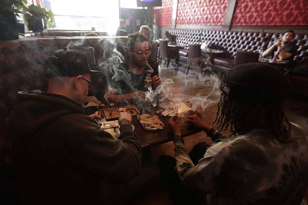 In this March 1, 2018, file photo, patrons at a San Francisco dispensary smoke marijuana. Legal ...
