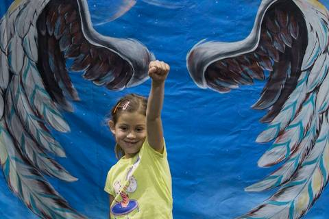 Amber Marica, 7, takes a photo in front of a trick art mural by family activity center HeadzUP ...