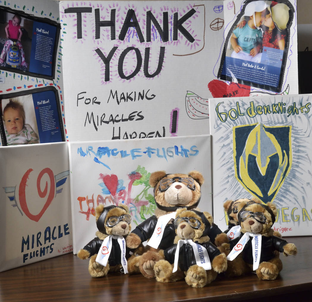 Miles the Bear mascots and a thank you poster and paintings are shown at the Miracle Flights of ...