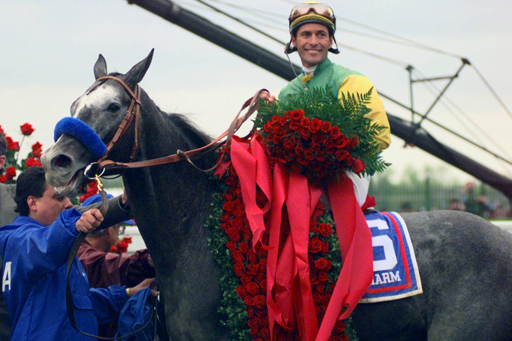 Jockey Gary Stevens and Silver Charm wear the signature roses in the winner's circle after winn ...