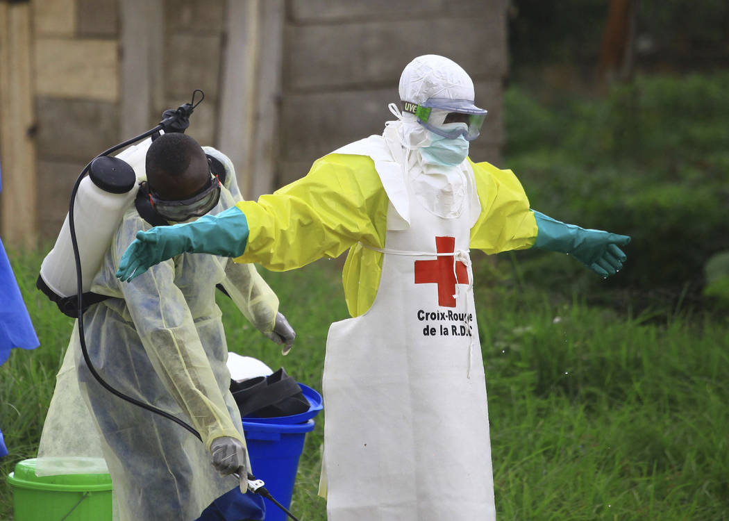 A health worker sprays disinfectant on his colleague after working Sept. 9, 2018, at an Ebola t ...