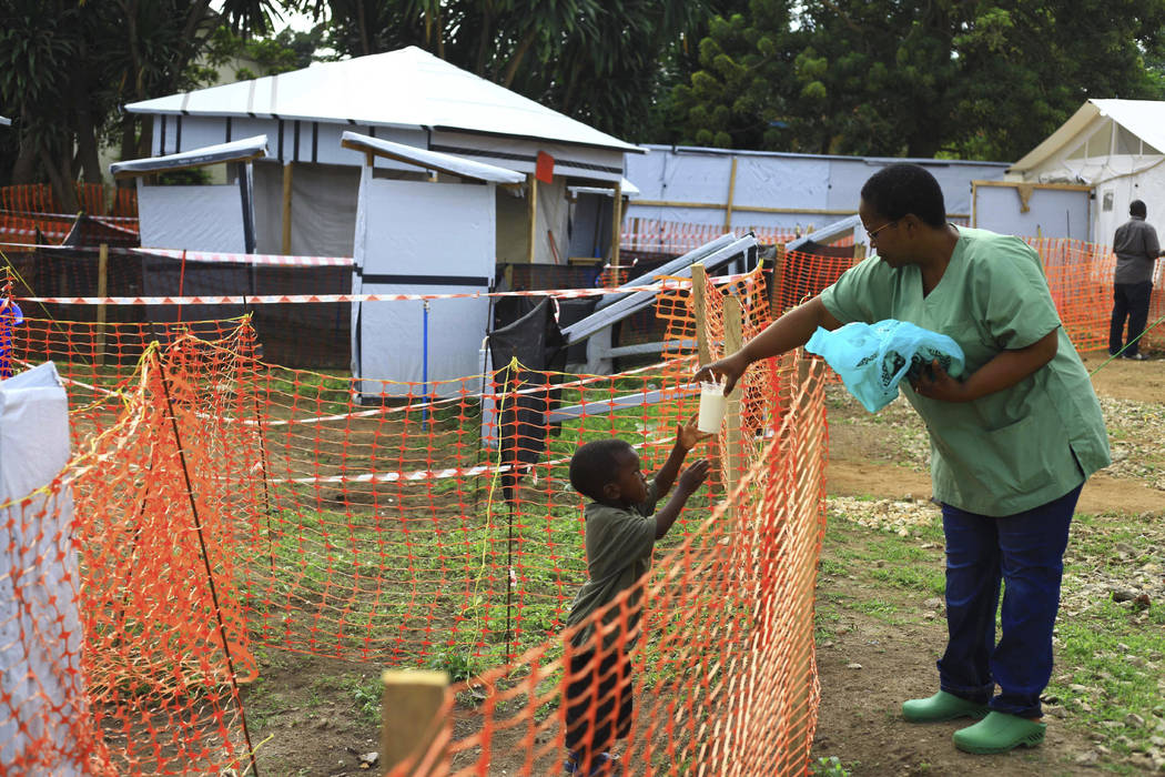 A health worker feeds a boy suspected of having the Ebola virus at an Ebola treatment centre in ...