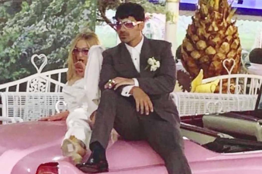 Sophie Turner and Joe Jonas pose on the hood of pink Cadillac after being married at the Little ...