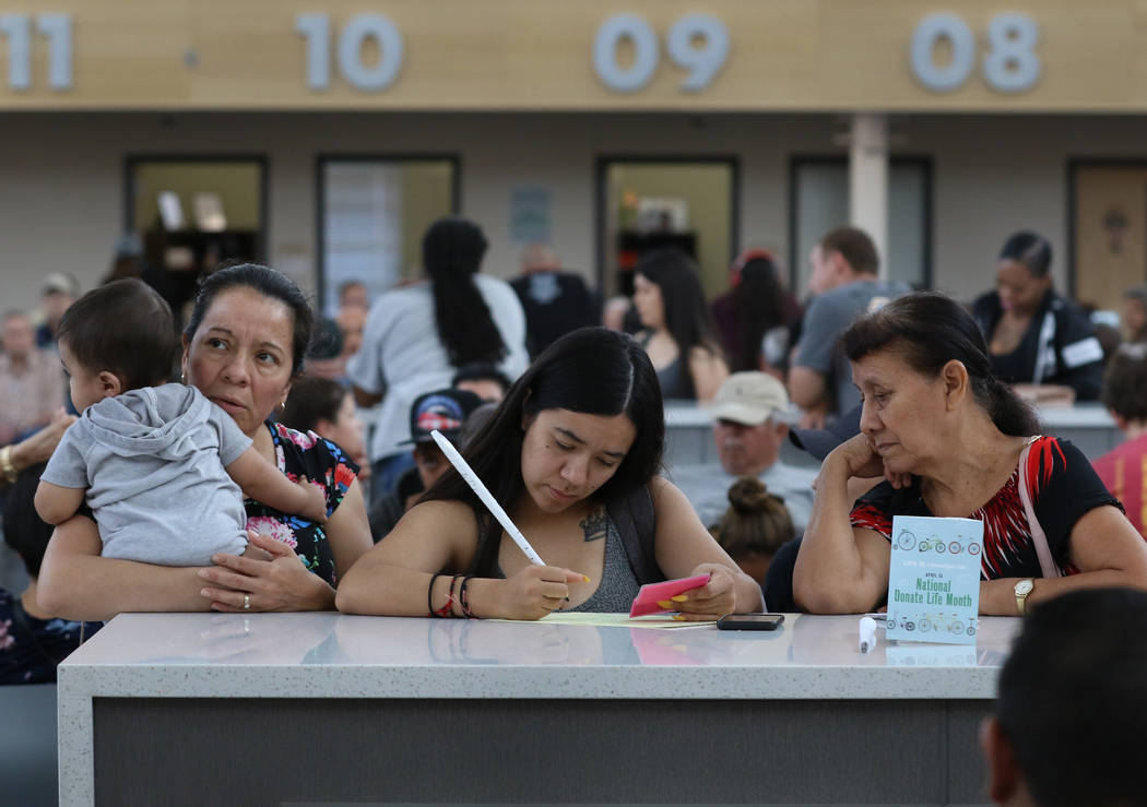 Customers, who declined to give their names, fill out forms at East Sahara DMV office on Friday ...
