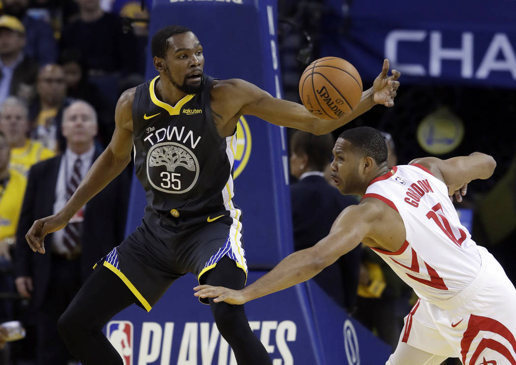 Golden State Warriors' Kevin Durant (35) is defended by Houston Rockets' Eric Gordon during the ...