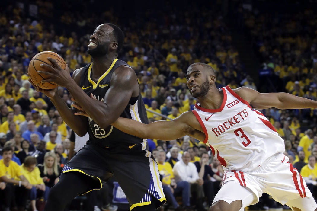 Golden State Warriors' Draymond Green, left, is defended by Houston Rockets' Chris Paul during ...