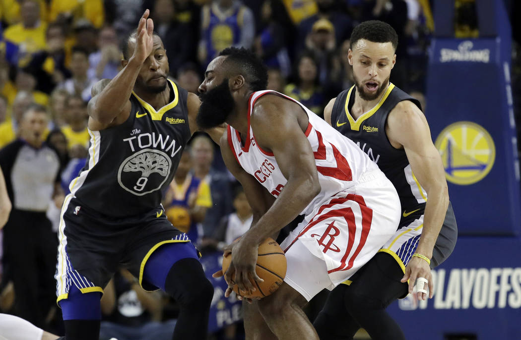 Houston Rockets' James Harden, center, is defended by Golden State Warriors' Andre Iguodala, le ...