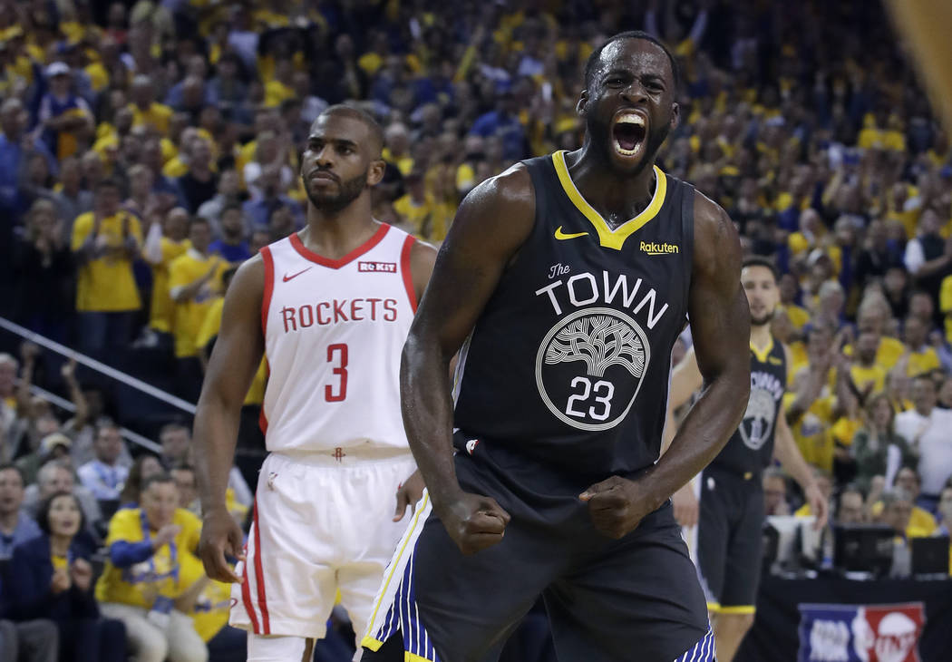 Golden State Warriors' Draymond Green (23) reacts after scoring, in front of Houston Rockets' C ...