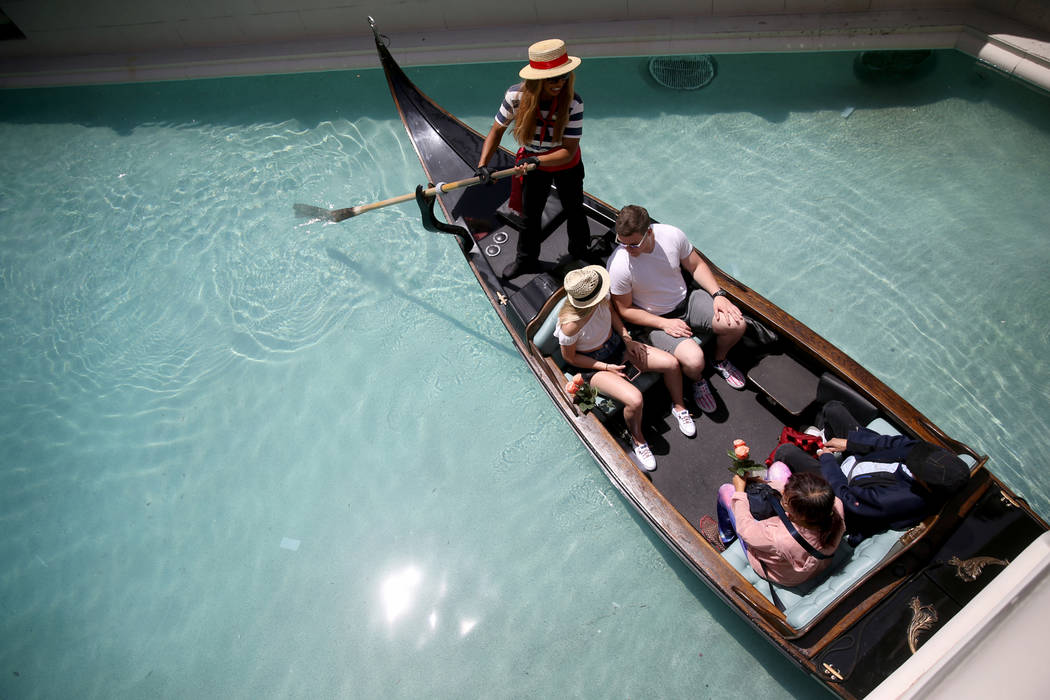 Shannon Terhaar and Layne Chapman of Minneapolis, top get a ride with gondolier Coco and free r ...