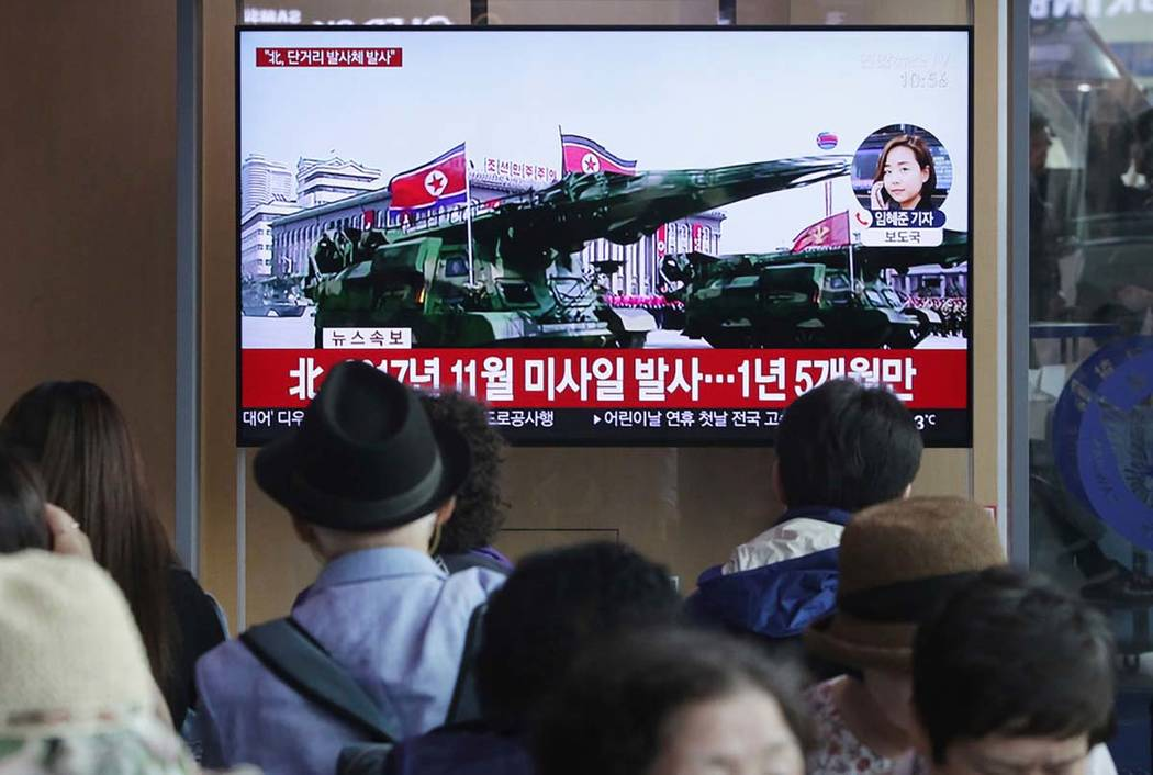 People watch a TV showing a file footage of North Korea's missiles during a military parade in ...