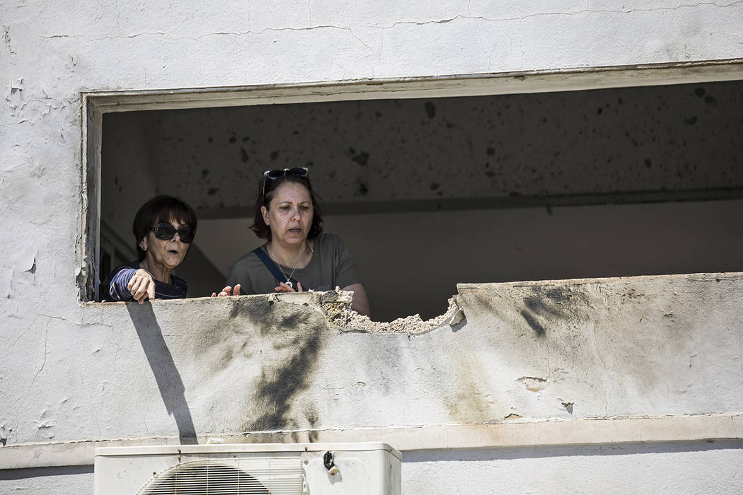 Women look at the damage caused by a rocket fired from Gaza that hit a house in a moshav in Isr ...