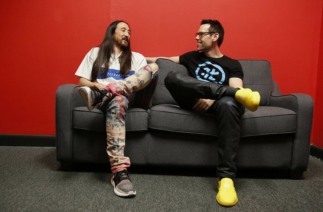Steve Aoki, left, and Tom Bilyeu, right, sit for a portrait during a comic book signing of his ...