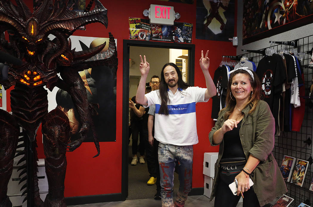 """Steve Aoki, center, gestures to his fans as he enters a comic book signing of his new """"Neo ..."""