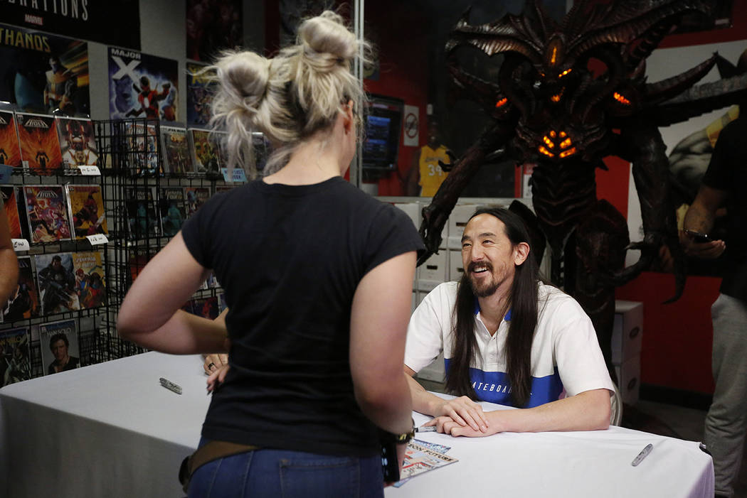 """Steve Aoki talks to a fan during a comic book signing of his new """"Neon Future"""" comic ..."""