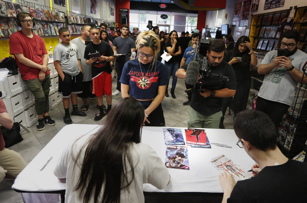 A large group of fans gather to get autographs from Steve Aoki during a comic book signing of h ...
