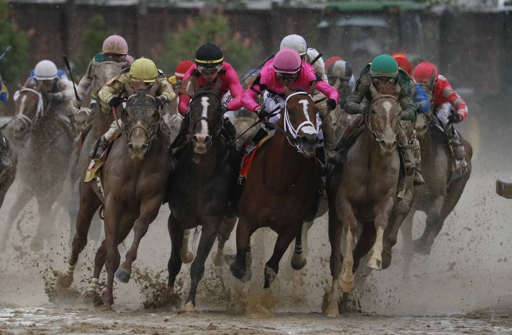 Luis Saez riding Maximum Security, second from right, goes around turn four with Flavien Prat r ...