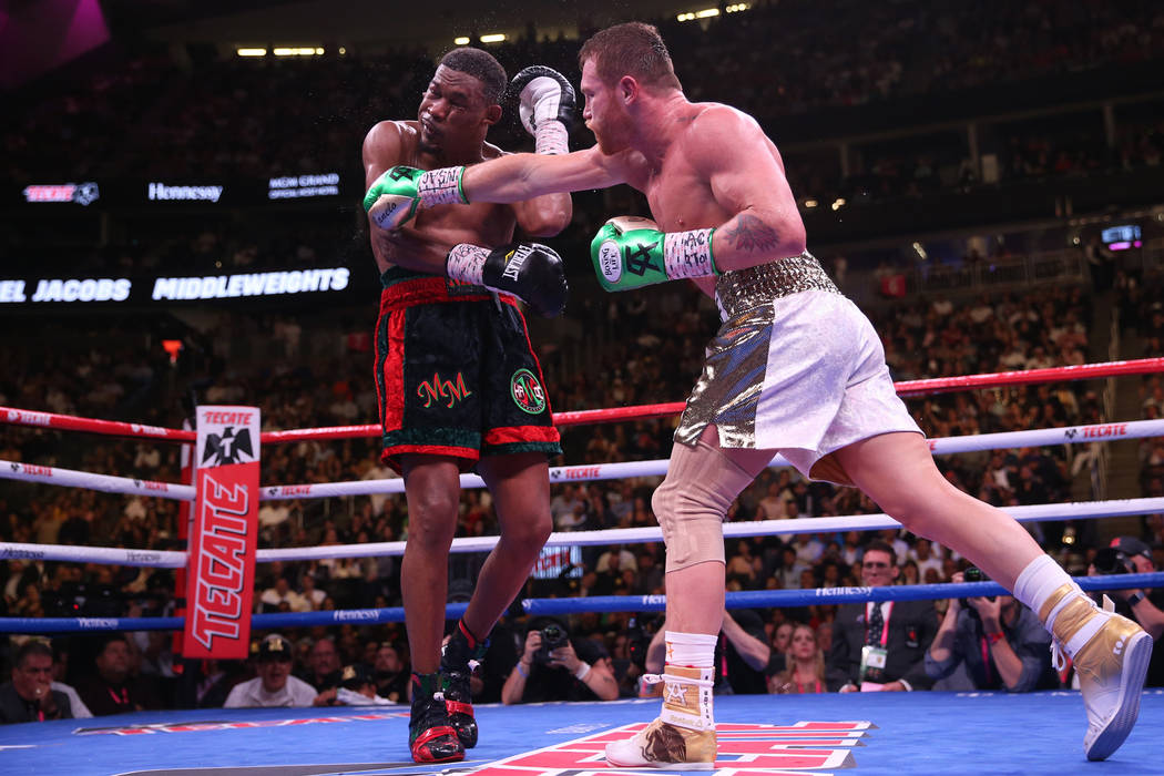 Saul Canelo Alvarez, right, connects a punch against Daniel Jacobs in the WBC, WBA, IBF, and Ri ...