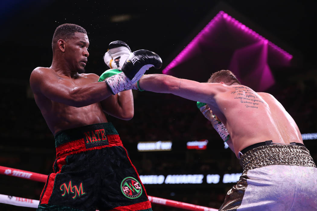 Saul Canelo Alvarez, right, throws a punch against Daniel Jacobs in the WBC, WBA, IBF, and Ring ...