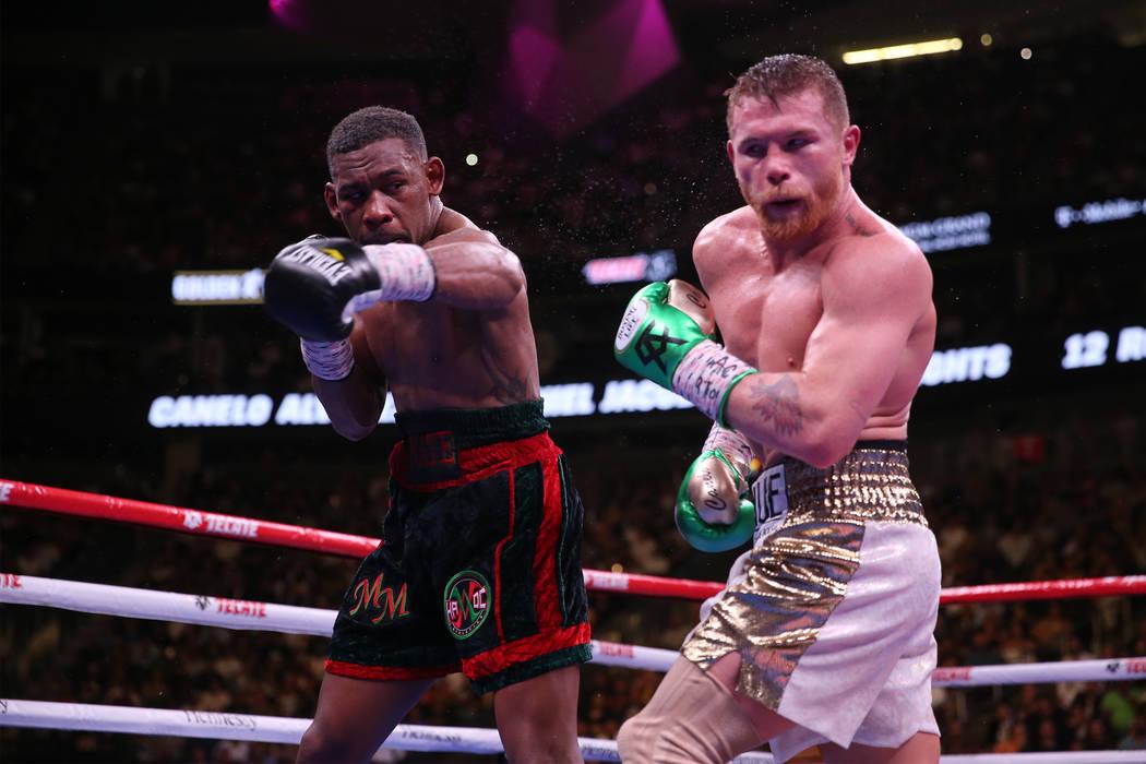 "Daniel Jacobs, left, throws a punch against Saul ""Canelo"" Alvarez in the WBC, WBA ..."