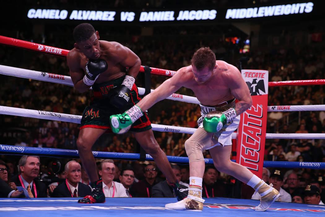 Saul ÒCaneloÓ Alvarez, right, throws a punch against Daniel Jacobs in the WBC, WBA, I ...