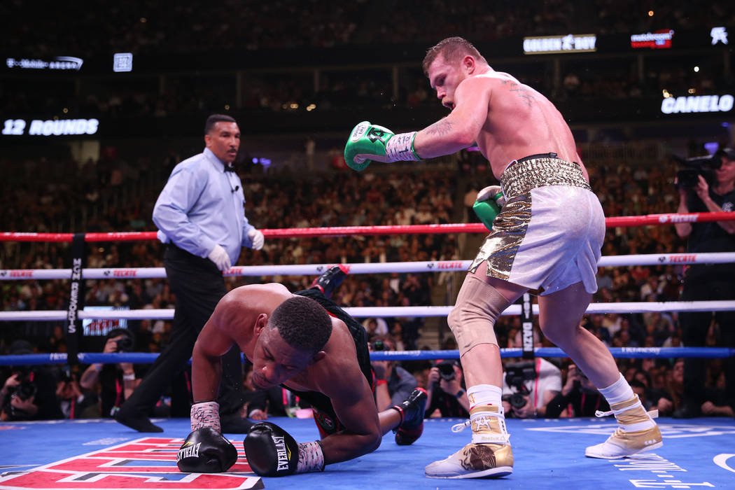 """Daniel Jacobs, left, slips on the ring during the 12th round against Saul """"Canelo&#x201d ..."""