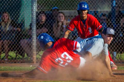 Liberty's Mason Bowden (1) looks on as teammate Ky Yamamoto (23) slides safely into home plate ...