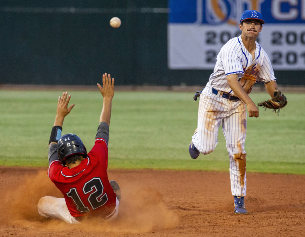 Las Vegas' Nathan Freimuth (12) slides late into second base as Reno's Gunner Gouldsmith (8) lo ...