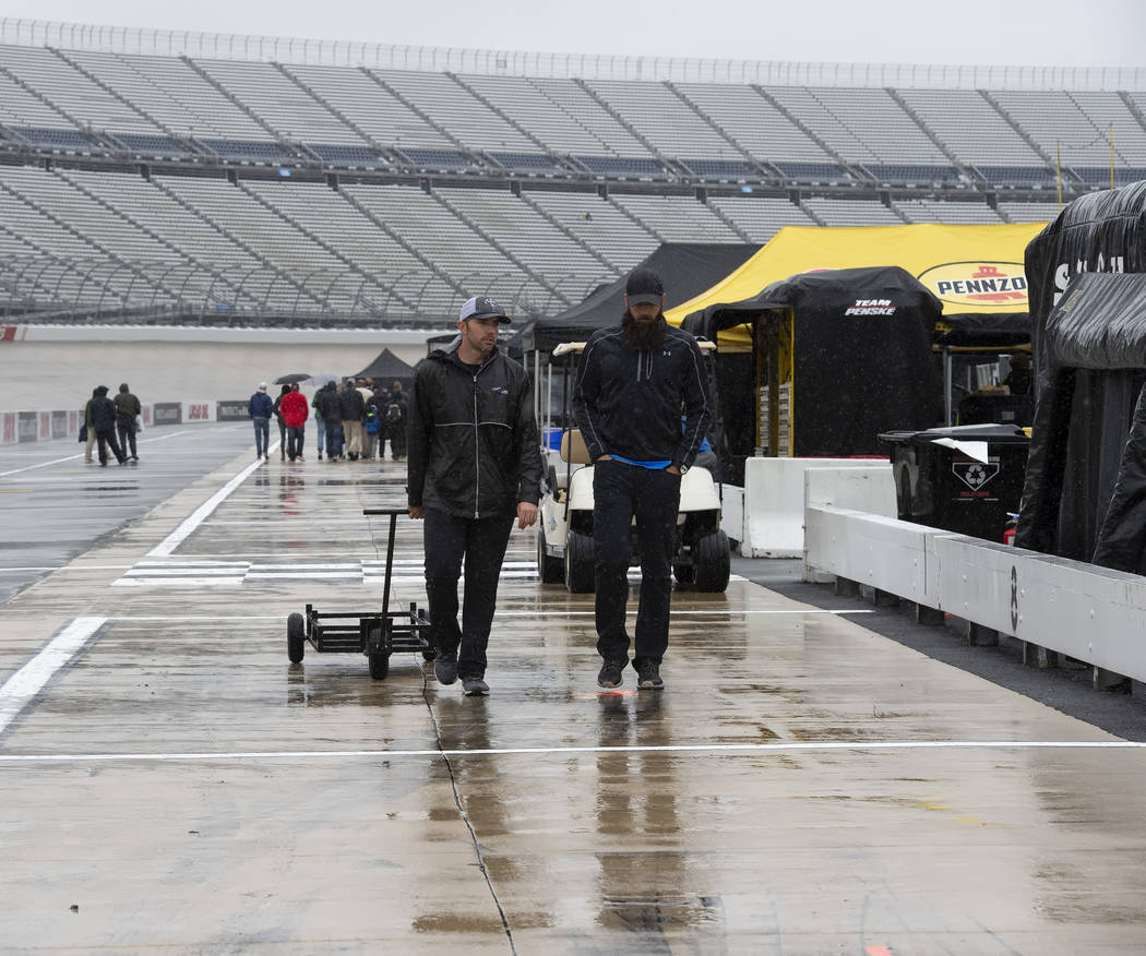 People walk in the pits area as rain falls before a NASCAR Cup series auto race at Dover Intern ...