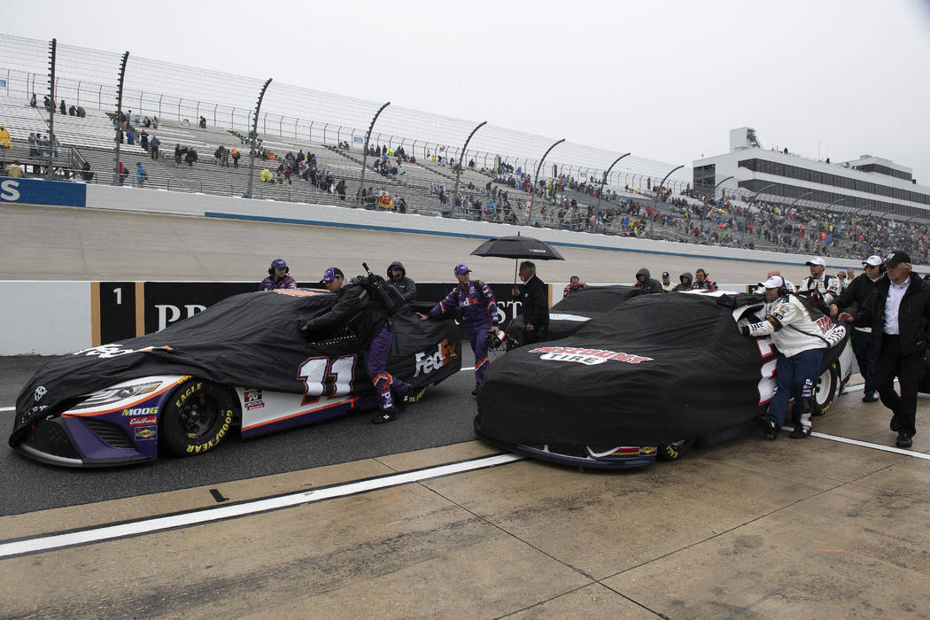 Teams push their cars down pit road after a NASCAR Cup Series auto race was postponed due to in ...