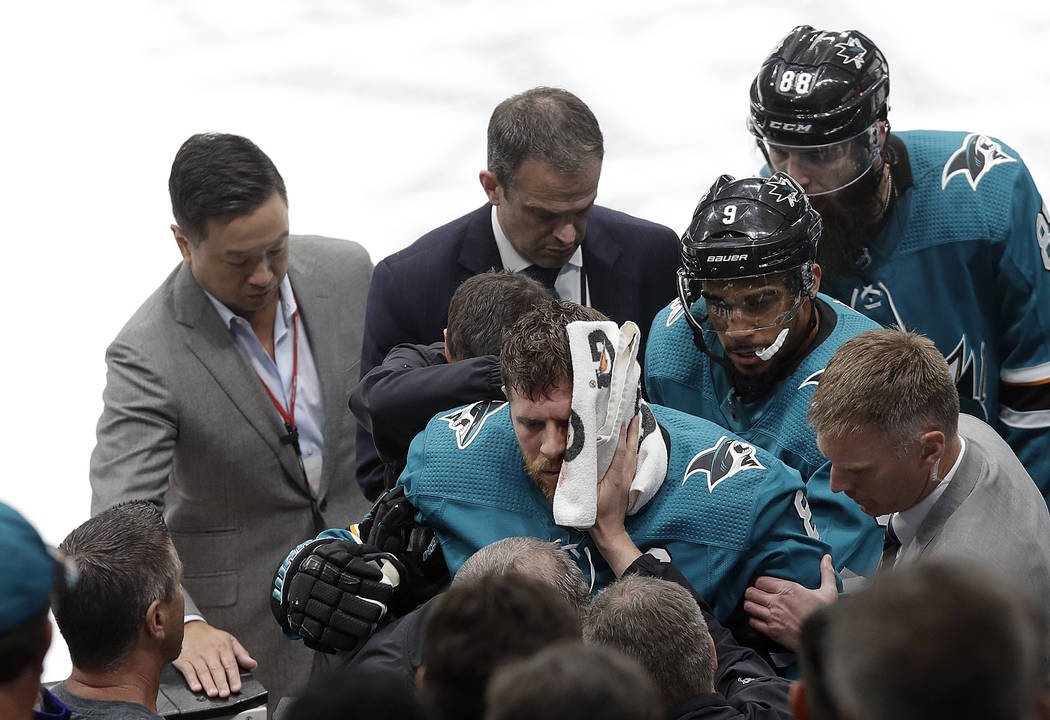 San Jose Sharks center Joe Pavelski, bottom center, is helped off the ice during the third peri ...