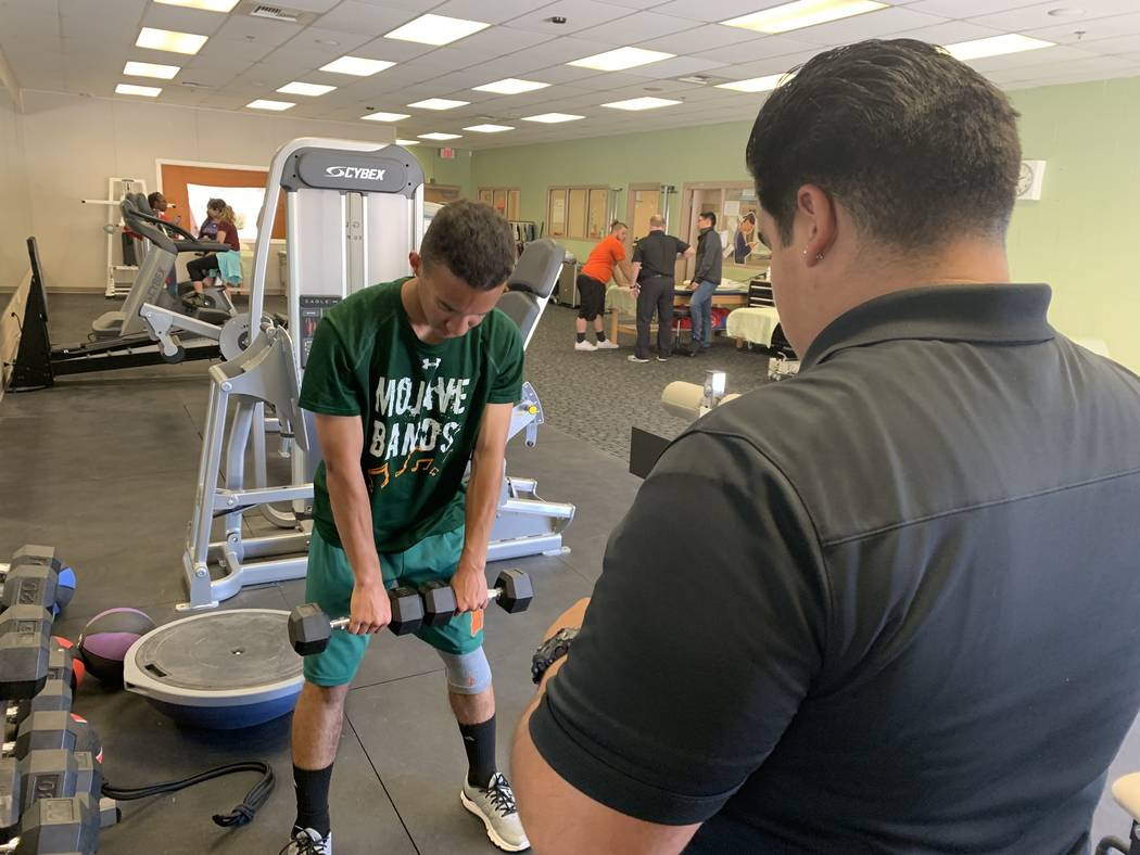 Donovan Davis, left, participates in physical therapy during his seventh period class with Ivan ...