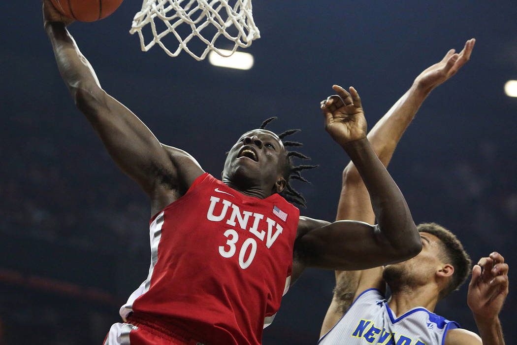 UNLV Rebels forward Jonathan Tchamwa Tchatchoua (30) takes a shot while under pressure from Nev ...