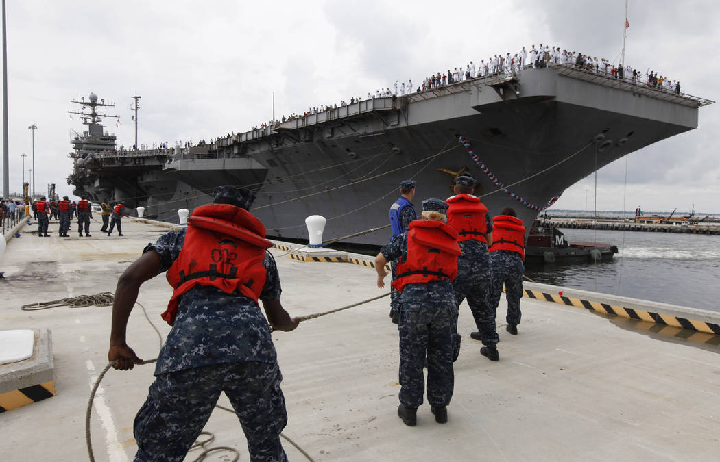 Navy shore crew haul in lines as the nuclear-powered aircraft carrier USS Abraham Lincoln arriv ...