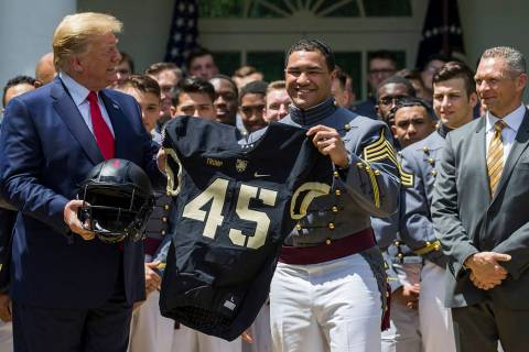 President Donald Trump accepts a jersey from Army running back Darnell Woolfolke Army during th ...