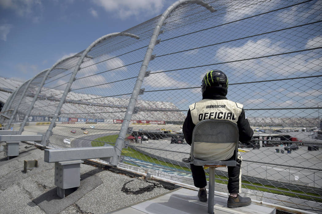 A NASCAR official looks on as drivers compete during the NASCAR Cup Series auto race, Monday, M ...