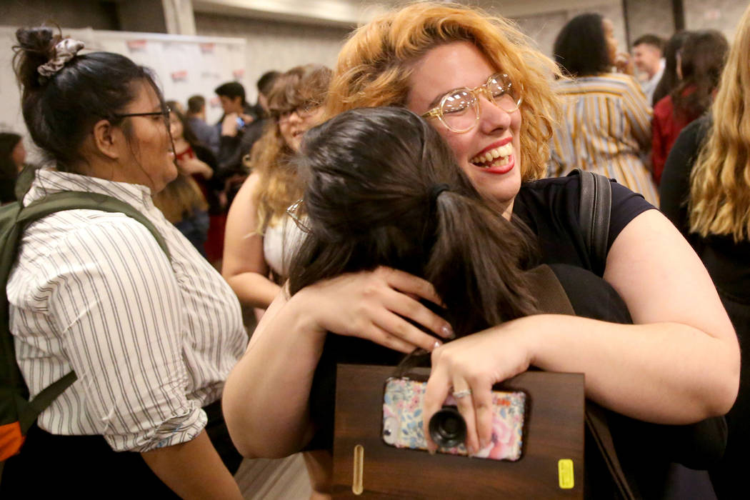 Laura Solsona of Spring Valley High School newspaper, The Grizzly Growler, facing, hugs Jessica ...