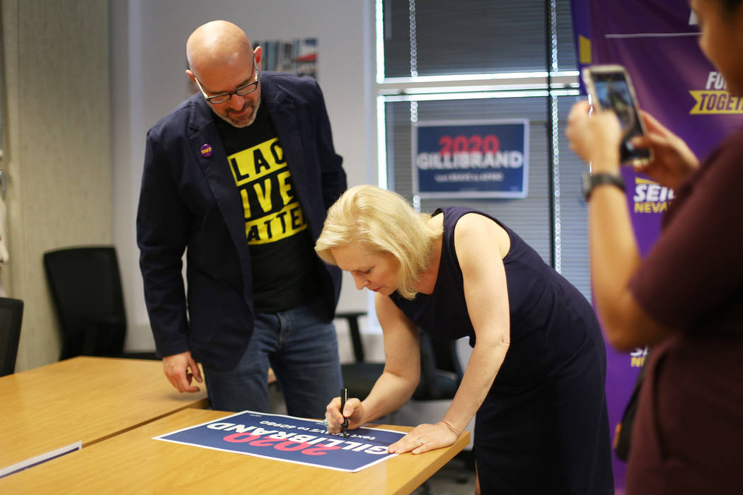 Democratic presidential candidate Sen. Kirsten Gillibrand signs a poster next to SEIU Local 110 ...