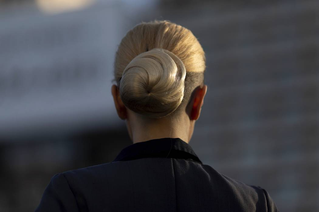 A woman wearing Eva Peron's characteristic top knot hairstyle parades in Buenos Aires, Argentin ...
