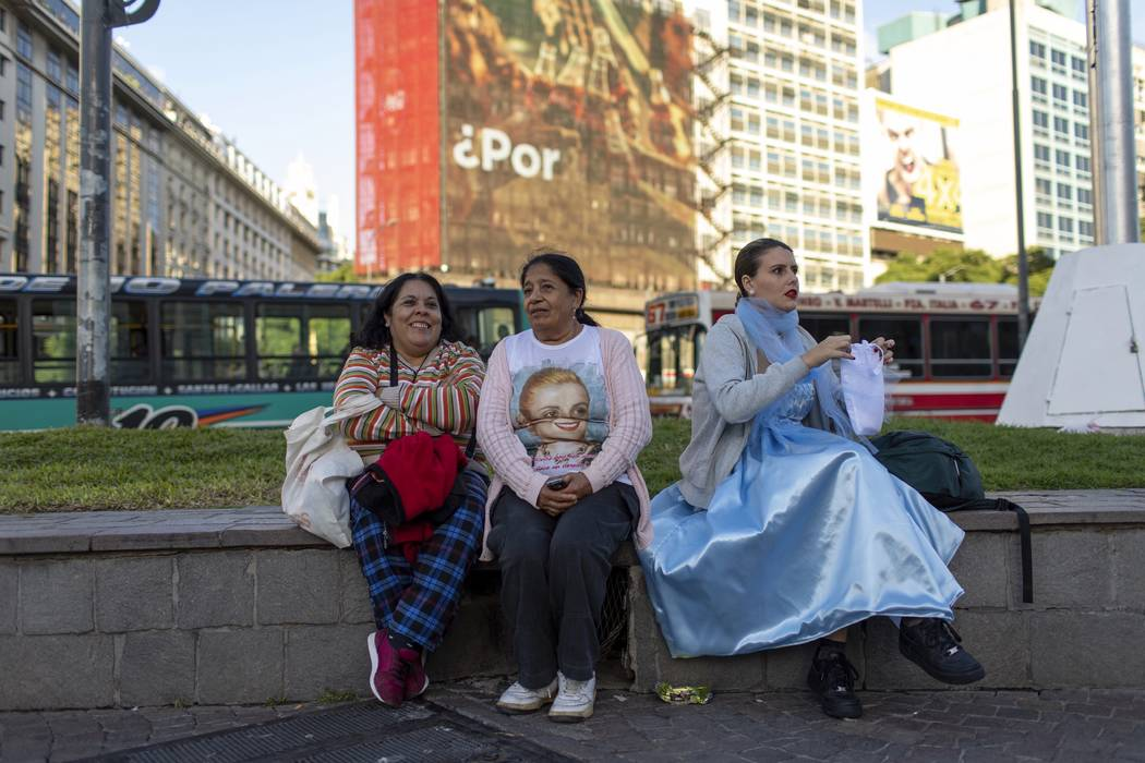 A woman dressed as Eva Peron sits next to other two women, in Buenos Aires, Argentina, Monday, ...