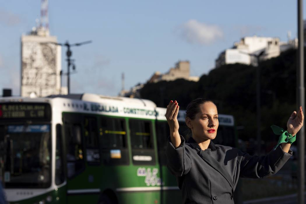 A women poses for photos dressed as Eva Peron in Buenos Aires, Argentina, Monday, May. 6, 2019. ...